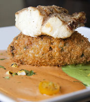 Grilled ling cod served with a tomato chipotle cream sauce, cilantro cream, and a California rice cake.
