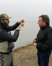 radio host Joe Getty interviewing farmer in flooded field