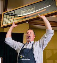 Circle of Life Sushi rolling contest winner holding samurai sword trophy