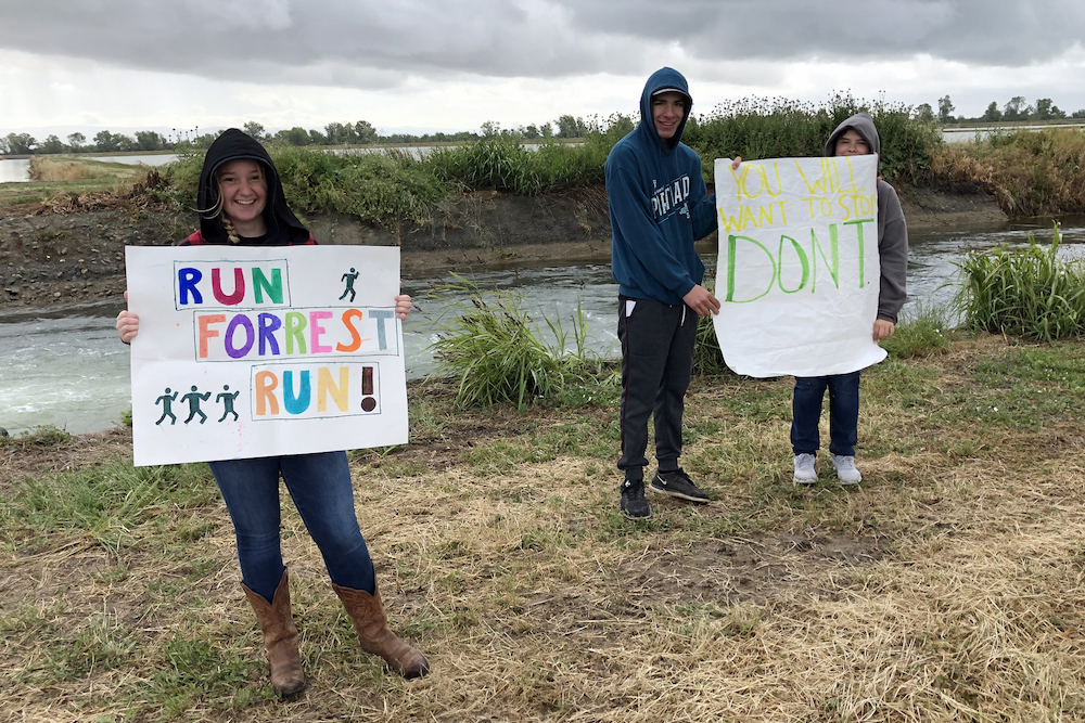people holding signs of support for runners