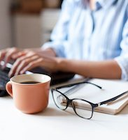 woman workplace in kitchen with laptop, cup of coffee, spectacles.